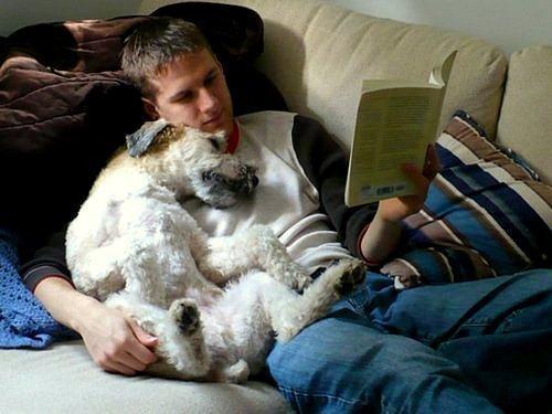 Homem lendo livro com cão