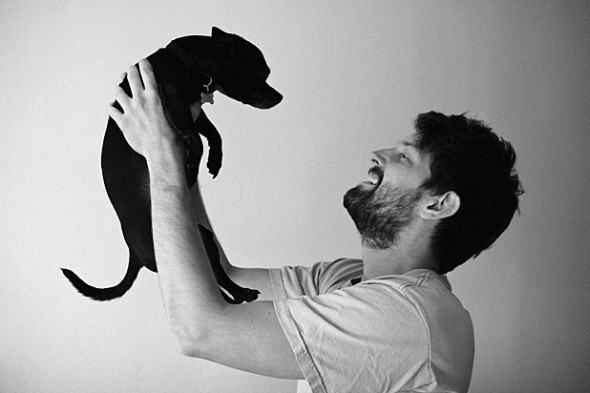 Homem levantando cão para o alto